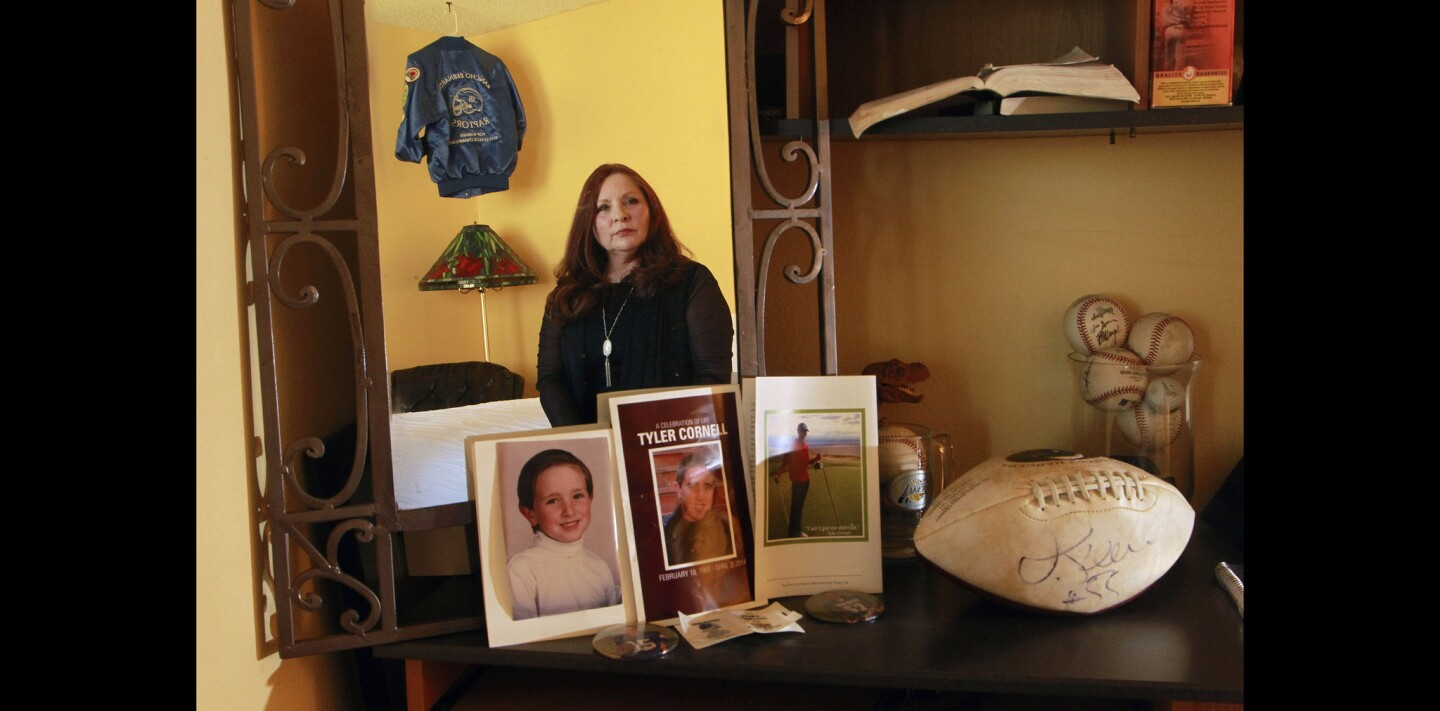 Jo Cornell is reflected in a mirror that has pictures of her son Tyler Cornell, including a kindergarten picture and the program for his memorial service, leaned against it with his football signed by former Chargers football player Junior Seau while she sits on her son's bed at her home in Rancho Bernardo.