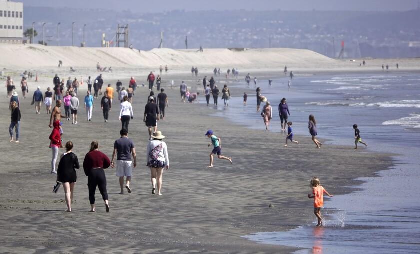 People walk along the beach in Coronado.