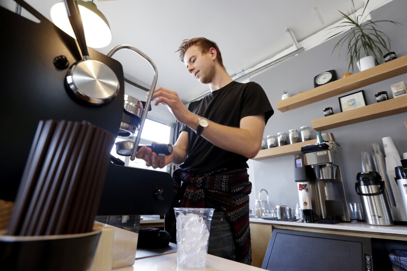 FILE - In this Nov. 4, 2019 file photo, barista Porter Hahn makes an iced coffee drink for a customer in a coffee shop in Seattle. U.S. services companies grew at a faster pace in February 2020 than the previous month, an indication that the economy is still expanding, despite growing concerns about global coronavirus outbreak. The Institute for Supply Management said Wednesday, March 4, 2020 that its service-sector index rose to 57.3 from 55.5 in January. (AP Photo/Elaine Thompson, File)
