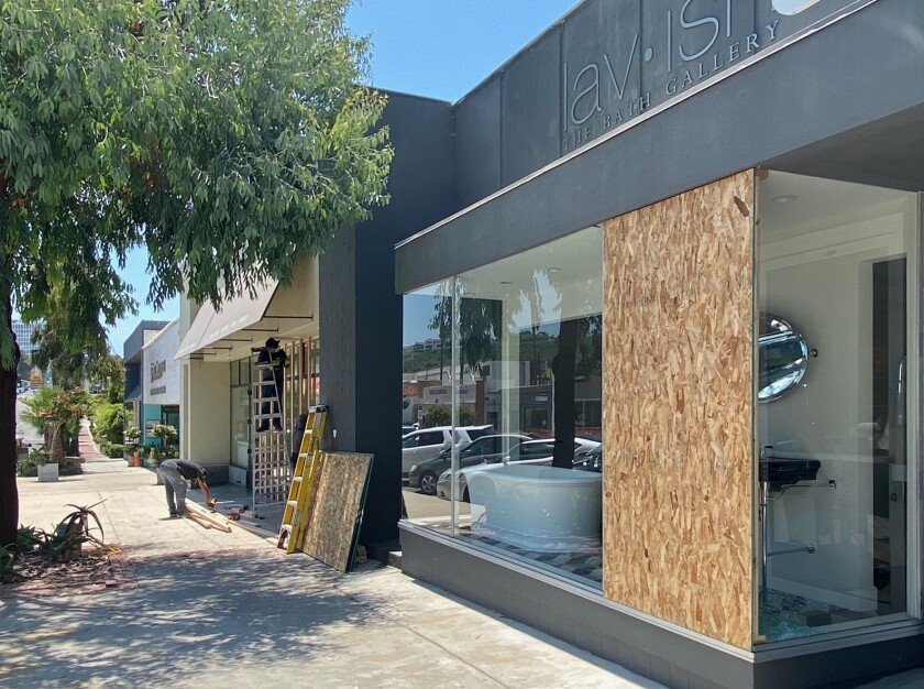 Workers board up smashed windows June 3 at Cabochon Tile & Stone, next to Lavish — The Bath Gallery, which also was damaged.