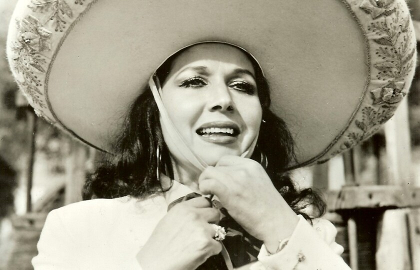 Flor Silvestre cinches up her sombrero in a movie scene