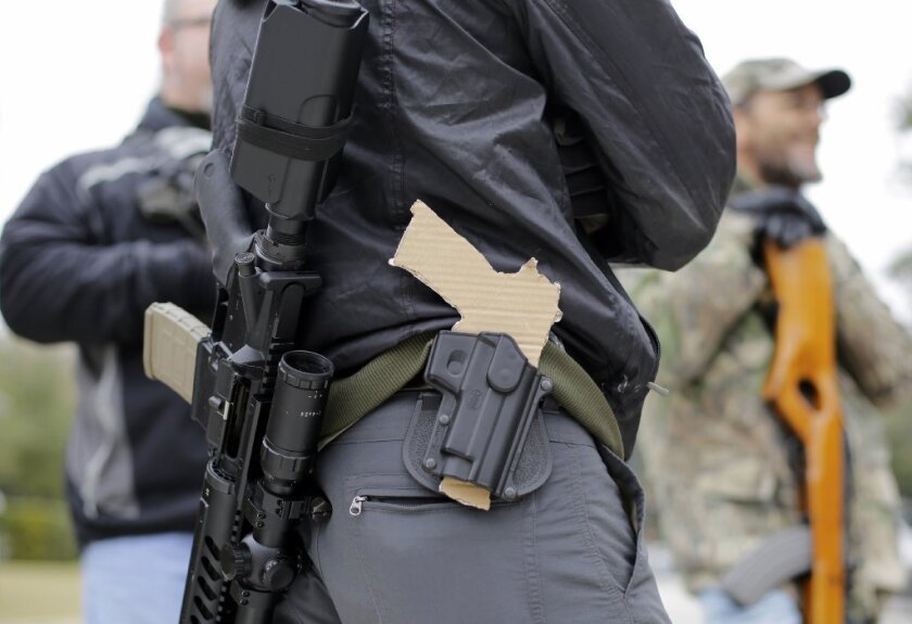 A gun rights advocate carries a rifle on his back and a cardboard cutout of a pistol on his waist outside the Texas Capitol. Lawmakers have approved a law allowing licensed gun owners to carry concealed firearms on college campuses.