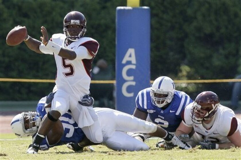 Virginia Tech quarterback Tyrod Taylor (5) scrambles to escape from Duke's Patrick Egboh during the first half of an NCAA college football game in Durham, N.C., Saturday, Oct. 3, 2009. (AP Photo/Gerry Broome)