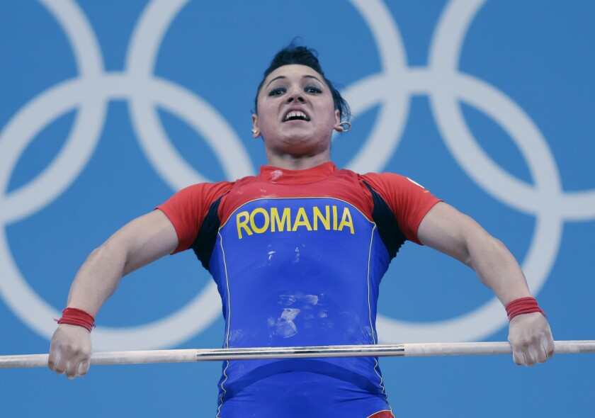 FILE - In this file photo dated Wednesday, Aug. 1, 2012, Romania's Roxana Cocos competes during the women's 69-kg weightlifting competition at the 2012 Summer Olympics, in London. A culture of alleged corruption among international weightlifting officials has been detailed in a 50-page investigative report released Thursday June 24, 2021, of covered-up doping cases, with Cocos stripped of her medal years later when re-tests revealed her steroid use.(AP Photo/Hassan Ammar, FILE)