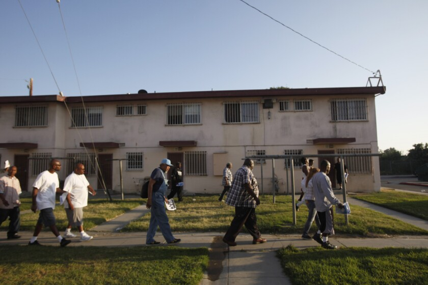 Members of Project Fatherhood walk through Jordan Downs in Watts to help spread the word about their program.