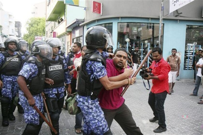 Maldivian police officers detain a journalist during a protest in Male, Maldives, Sunday, May 1, 2011. Maldives' police have used tear gas and batons to break up the protest demanding that President Mohamad Nasheed step down. Dozens of people have been arrested.(AP Photo/Sinan Hussain)