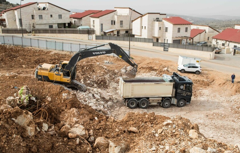 Palestinian laborers work at the construction site of a new housing project in the Israeli settlement of Ariel near the West Bank city of Nablus on Jan. 25, 2017.