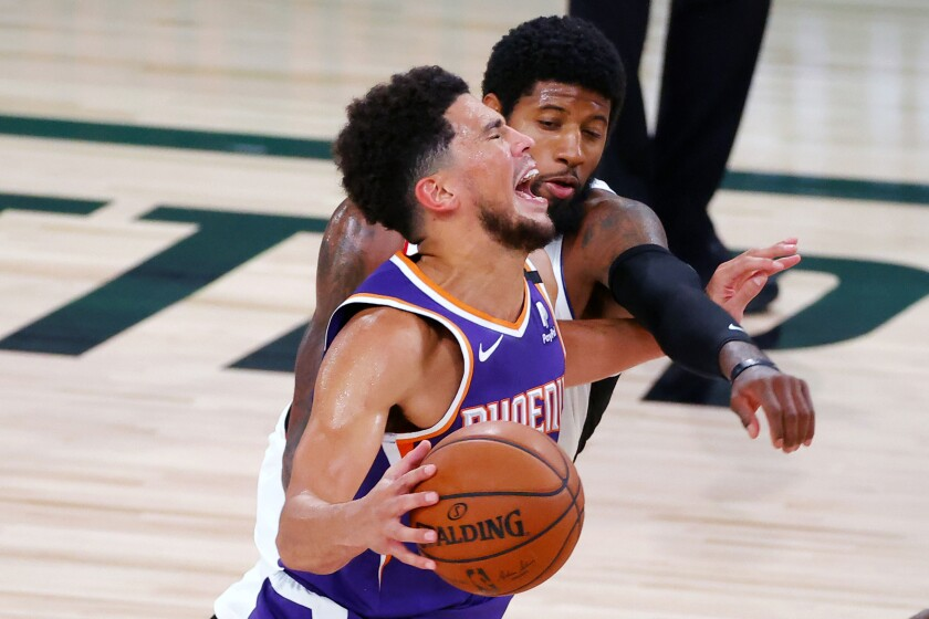 Phoenix Suns' Devin Booker draws a foul from Los Angeles Clippers' Paul George, rear, during an NBA basketball game Tuesday, Aug. 4, 2020, in Lake Buena Vista, Fla. (Kevin C. Cox/Pool Photo via AP)