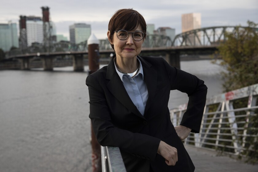 Sarah Iannarone stands along the Willamette River in Portland with the Hawthorne Bridge in the background.