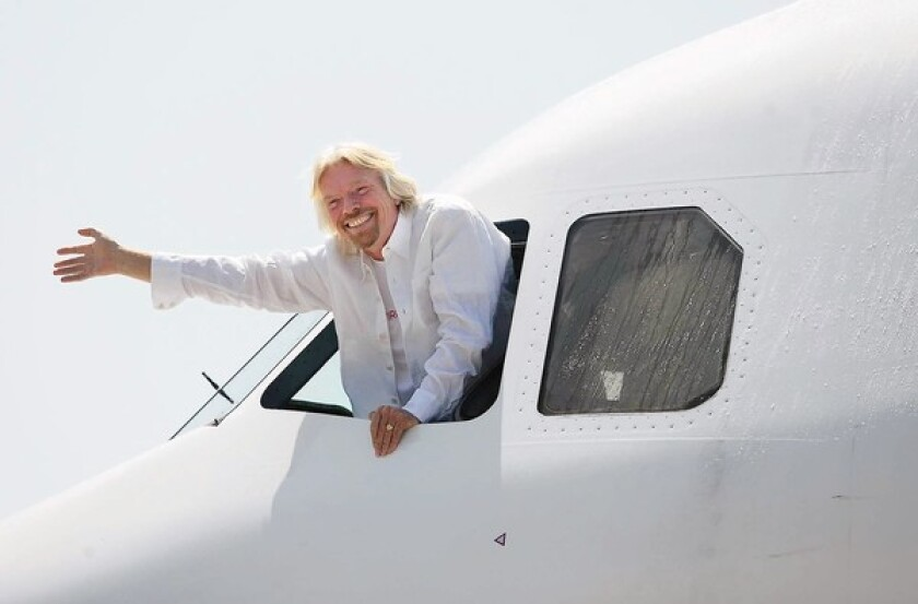 Virgin founder Sir Richard Branson waves to the crowd upon arrival at John Wayne Airport to celebrate the Virgin America flight service route from San Francisco to Orange County in 2009. (DON LEACH, Daily Pilot / January 24, 2011)