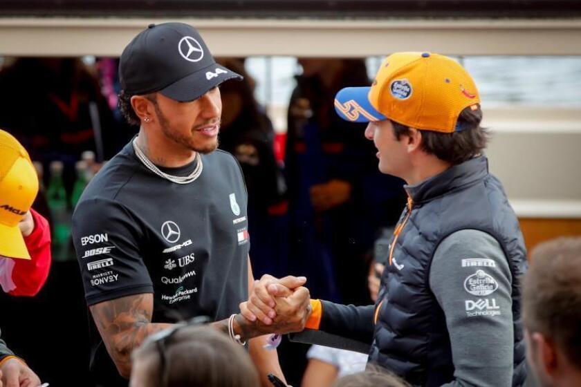 El piloto británico Lewis Hamilton (i), de la escudería Mercedes, saluda al español Carlos Sáinz, de McLaren, durante un acto celebrado este miércoles en la Plaza Federación de Melbourne, en Australia. EFE