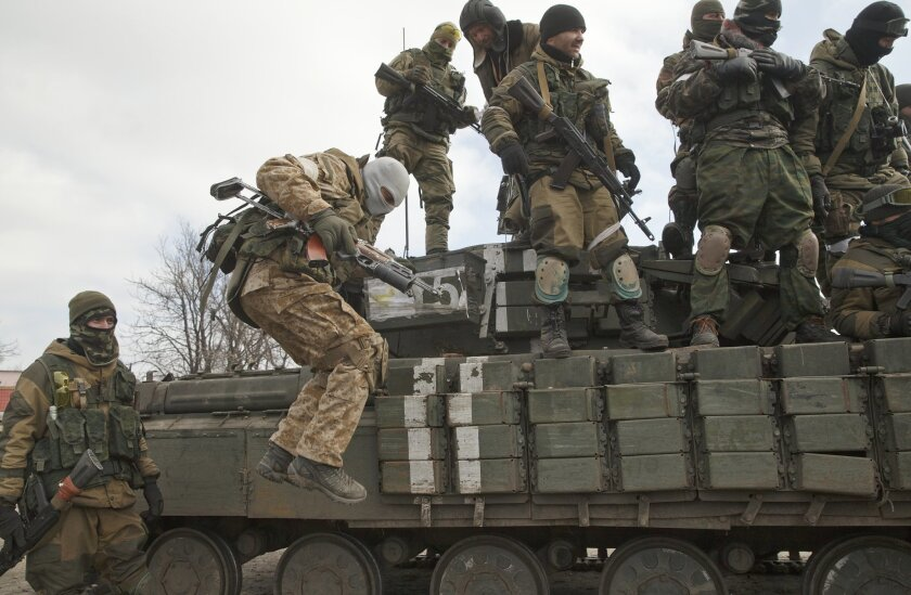 A Russia-backed rebel jumps off a tank in Debaltseve, Ukraine, Friday, Feb. 20, 2015. After weeks of relentless fighting, the embattled Ukrainian rail hub of Debaltseve fell Wednesday to Russia-backed separatists, who hoisted a flag in triumph over the town. The Ukrainian president confirmed that he had ordered troops to pull out and the rebels reported taking hundreds of soldiers captive.(AP Photo/Vadim Ghirda)