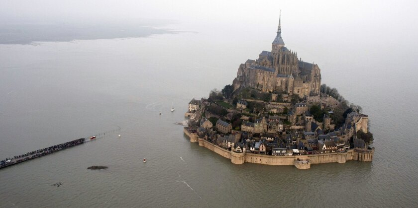 This March 21, 2015 aerial view shows a high tide submergeing a narrow causeway leading to the Mont Saint-Michel, on France's northern coast. French President Francois Hollande is scheduled to visit this unusual Atlantic fortress and tourist site of Mont Saint Michel, an island at high tide and a p