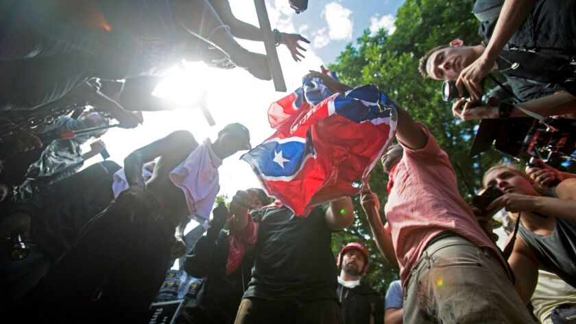FILE - In this Aug. 12, 2017 file photo, counter-protesters tear a Confederate flag during a white n