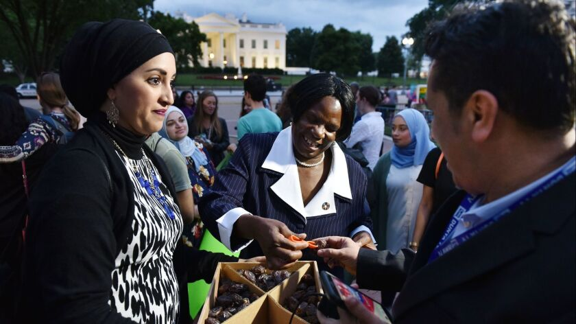 A woman offers dates, a traditional way to break the day's fast during Ramadan, on June 6 in Washington. Inside the White House, President Trump was hosting an iftar, but didn't invite American Muslims.