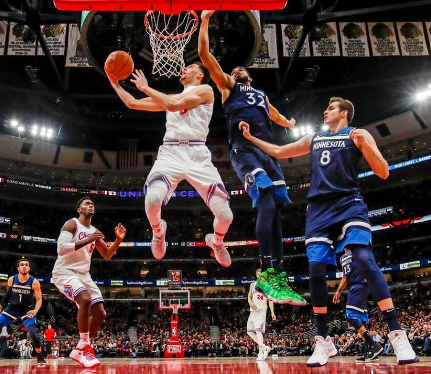 Chicago Bulls guard Zach LaVine (2L) shoots against Minnesota Timberwolves center Karl-Anthony Towns (2R) and Minnesota Timberwolves forward Nemanja Bjelica of Serbia (R) as Chicago Bulls forward Bobby Portis (L) watches in the second half of their NBA game at the United Center in Chicago, Illinois, USA, 09 February 2018. EFE