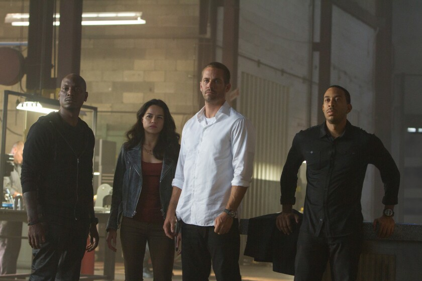 "Tyrese Gibson, left, Michelle Rodriguez, Paul Walker and Chris ""Ludacris"" Bridges in ""Furious 7."" After Walker's death, the franchise's future was in doubt but ultimately continued without him."