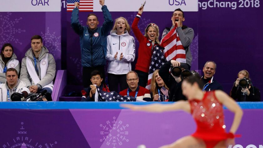 Mirai Nagasu of the competes in figure skating's team event as Ramona's Chris Knierim (standing, right) and her teammates cheer.