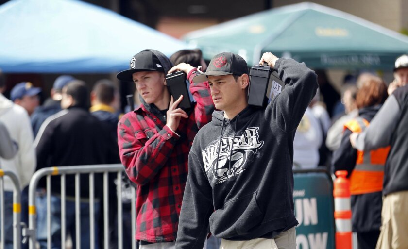 Dylan Marugg, left, and friend Chris Valluzzi carry 1000 rounds of 9mm ammo apiece from the gun show where better pricing and sheer availability drew many attendees.