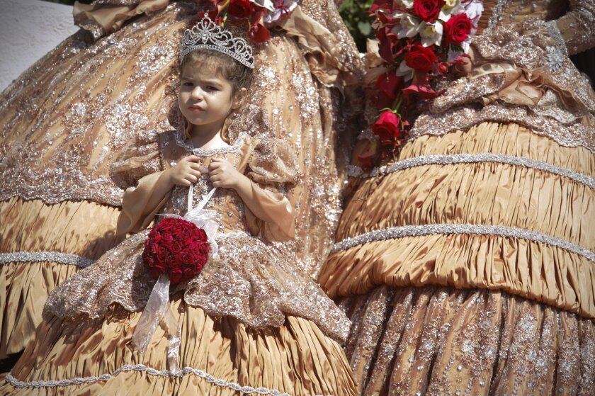Three-year-old Giabella Virissimo waits for the second portion of the parade celebrating the 104th Festa do Divino Esprito Santo. Photo by Howard Lipin/U-T San Diego