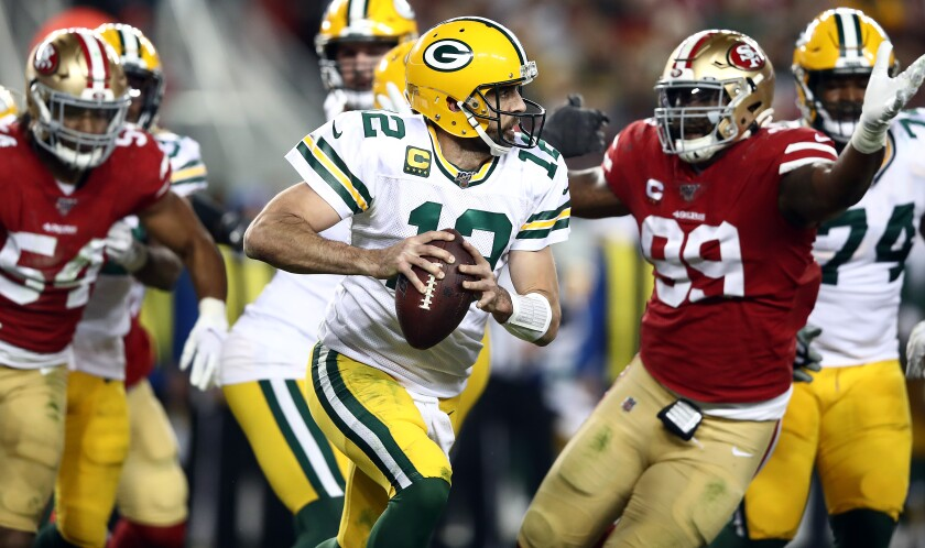 Packers quarterback Aaron Rodgers scrambles from the 49ers pass rush during a game Nov. 24, 2019, at Levi's Stadium in Santa Clara.