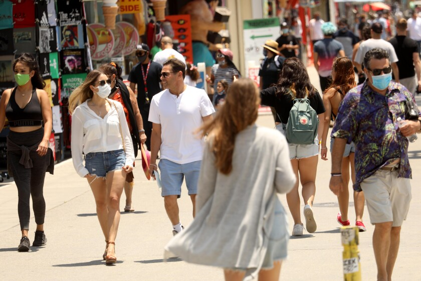 People, some with masks and others without, walk along the Venice Boardwalk earlier this month.