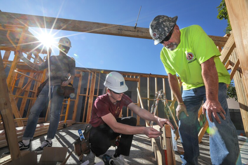 At the Warrior Village construction site at San Marcos High School, project instructor Alan Jurgensen of Associated General Contractors (right) gives advice to San Marcos High students Nick Przesmicki (center) and Cole Bradley as they work on a roof truss.