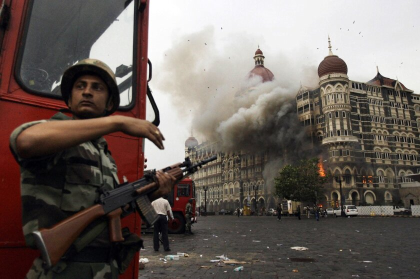 FILE- In this Nov. 29, 2008, file photo, an Indian soldier takes cover as the Taj Mahal hotel burns during gun battle between Indian military and militants inside the hotel in Mumbai, India. A Pakistani-American who helped plan a 2008 attack on India's financial hub has told a court in India that h