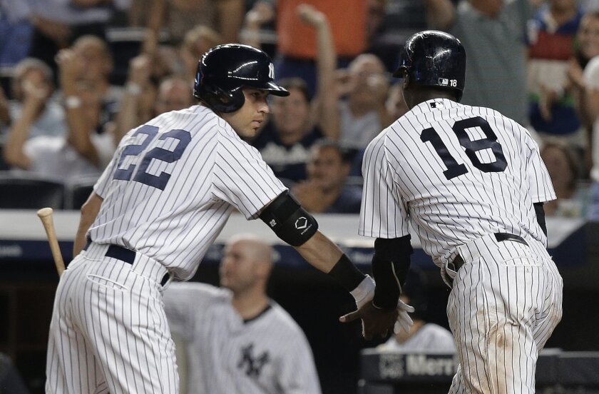 New York Yankees' Jacoby Ellsbury (22) greets Didi Gregorius after Gregorius scored on a double by Brendan Ryan during the sixth inning of a baseball game against the Baltimore Orioles, Tuesday, July 21, 2015, in New York. (AP Photo/Julie Jacobson)