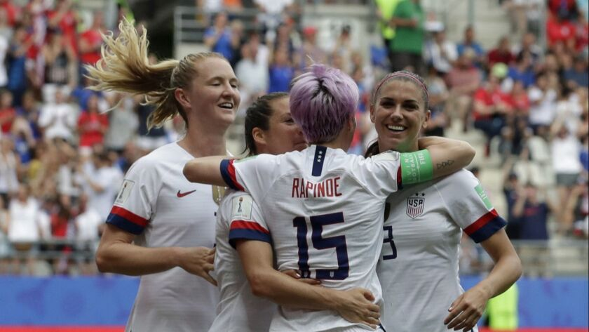United States' Megan Rapinoe, front, celebrates with teammates after scoring the opening goal from a