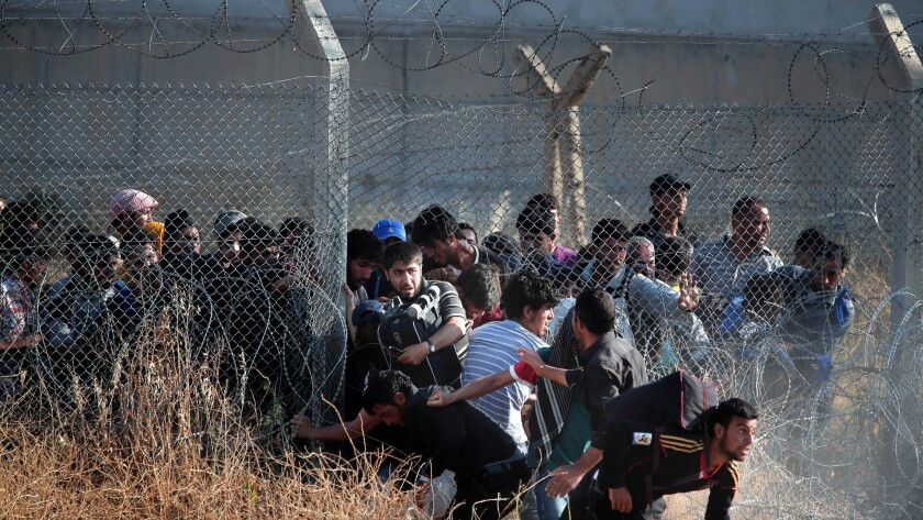 Syrian refugees burst into Turkey after breaking through a border fence and crossing the boundary separating the two countries in this June 14, 2015 photo. Turkey has been building a concrete wall along parts of the border in recent years.
