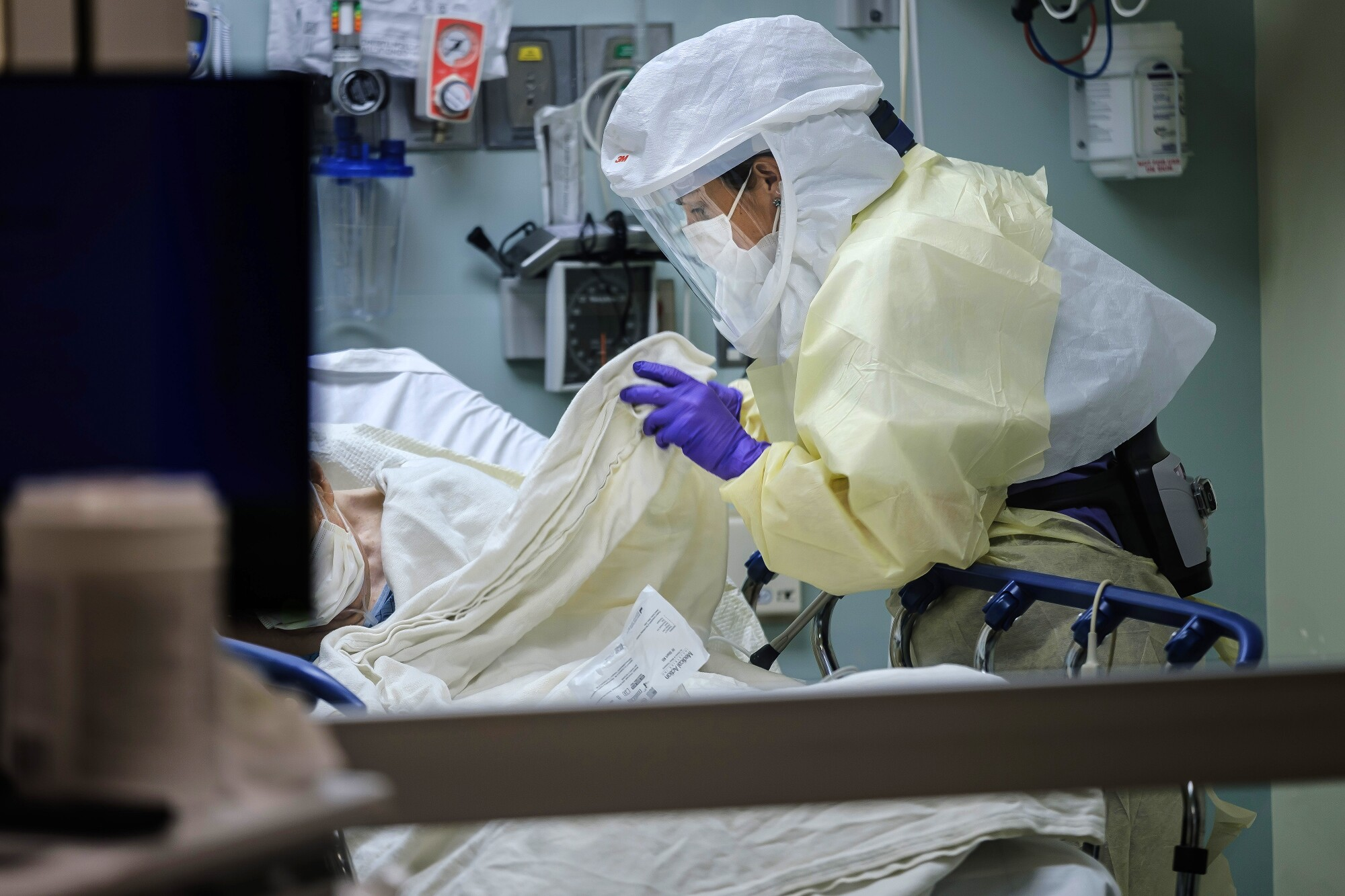 Wearing personal protective equipment, RN April Bandi, cares for a patient under investigation that have possible COVID-19 symptoms, inside a special negative pressure isolation room at the Emergency Department, at Sharp Memorial Hospital in San Diego, Calif., on April 10, 2020.