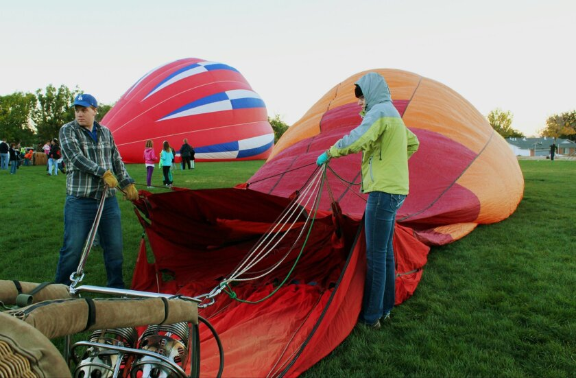 "Crew members of the hot air balloon dubbed ""First Light,"" prepare to inflate the envelope during the Aloft event at S.Y. Jackson Elementary School, marking the first official event of this year's Albuquerque International Balloon Fiesta in Albuquerque, N.M., Friday, Oct. 3, 2014. The nine-day fiesta gets underway Saturday, Oct. 4, 2014, with a mass ascension of hundreds of balloons at balloon fiesta park. (AP Photo/Susan Montoya Bryan)"