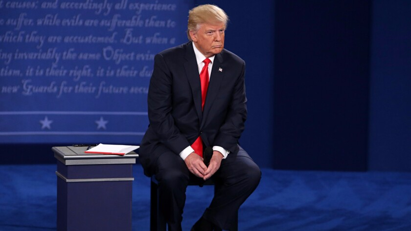 Donald Trump listens as Hillary Clinton addresses the crowd during the second debate between the two candidates on Oct. 9 at Washington University in St. Louis, Mo.