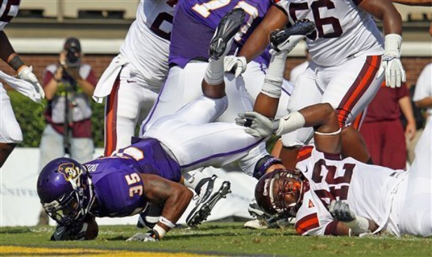 East Carolina's Michael Dobson (35) dives over Virginia Tech's J.R. Collins (42) for a touchdown during the first half of an NCAA college football game in Greenville, N.C., Saturday, Sept. 10, 2011. (AP Photo/Karl DeBlaker)