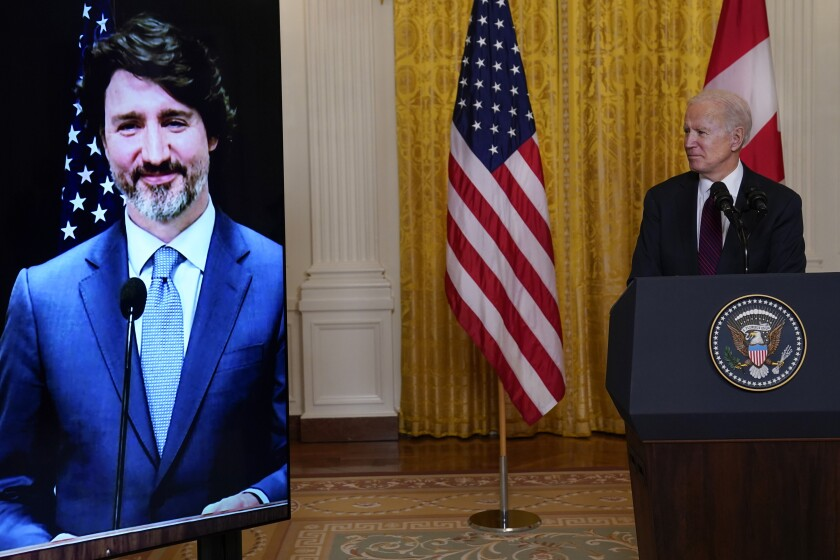 President Biden watches Canadian Prime Minister Justin Trudeau on a screen.