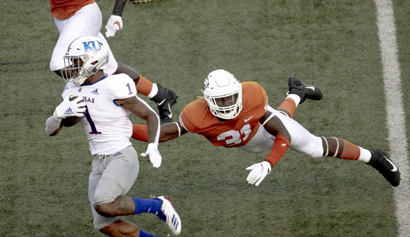 "FILE - In this Oct. 19, 2019, file photo, Texas' DeMarvion Overshown (31) leaps to tackle Kansas running back Pooka Williams Jr. (1) during an NCAA college football game in Austin, Texas. Texas junior linebacker Overshown announced Thursday, July 2, 2020, he will sit out all team activities until the school starts making campus changes sought by dozens of football players and other Longhorns athletes. The demands made in early June include renaming several campus buildings currently named after former Texas officials with ties to the Confederacy and segregation, and a call to drop the school song ""The Eyes of Texas."" (Nick Wagner/Austin American-Statesman via AP, File)"