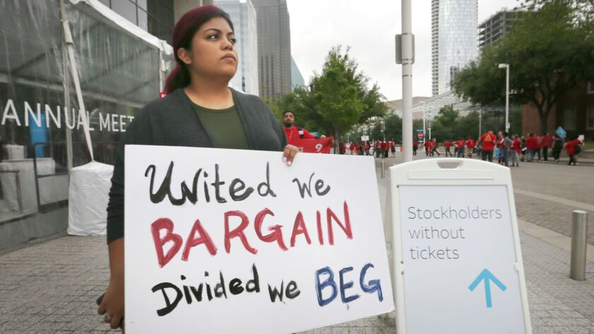 Kristian Hernandez, a member of the CWA, protests outside the AT&T shareholders meeting in Dallas la