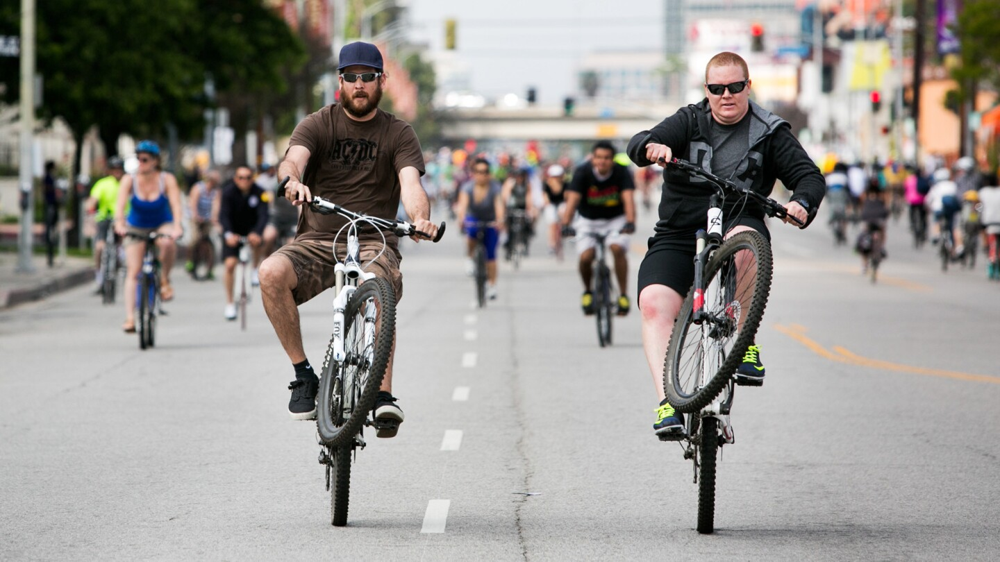 Riders perform wheelies as they ride down Lankershim Blvd. during CicLAvia.