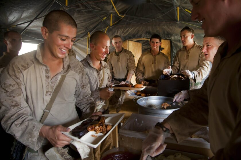 Cpl. Patrick Perez (left) and Cpl. Irvin Portugal from 1st platoon, Echo Company operating out of forward operating base Shir Ghazay get their July Fourth dinner.
