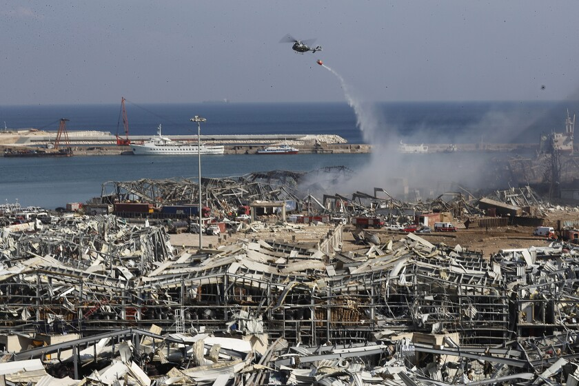 A Lebanese army helicopter throws water at the scene where an explosion hit of Beirut on Wednesday, Aug. 5, 2020.