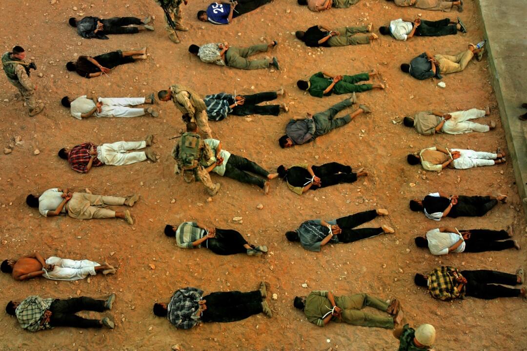 ردیف مردان روی زمین دراز کشیده و دستان خود را از پشت بسته اند