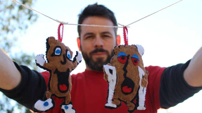 The artist Billy Kheel with his hand crafted Happy Foot and Sad Foot ornaments, $25, based on the ch