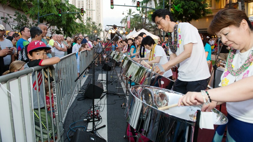 Playing their steel drums, the Pan Village All-Stars entertain the crowd along Waikiki's Kalakaua Avenue during the Pan-Pacific Festival.