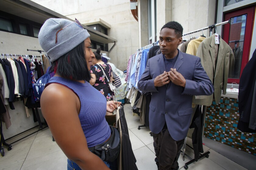 Keenan Gore, who is homeless, tries on a suit while his fiancée Cheyanne Cobb looks on at the Spring Into a New You career and resource fair at the San Diego Central Library on April 2. The event was held in partnership with the San Diego Workforce Partnership and the nonprofit Think Dignity, which provides services for homeless people.