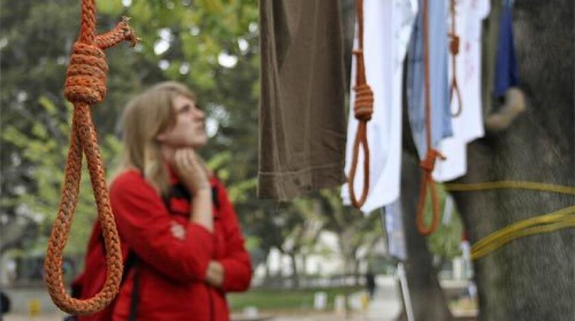 Sarah Stoker reads t-shirts displaying anti-hate messages. The nooses were hung anonymously the night before a tolerance rally.