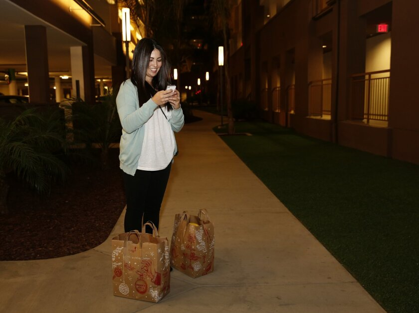 Alexis Fox, a delivery person for the the online grocery delivery service that delivers from Trader Joe's and Whole Foods, checks for directions to a Casa Mira View apartment as she makes her way to a home delivery.