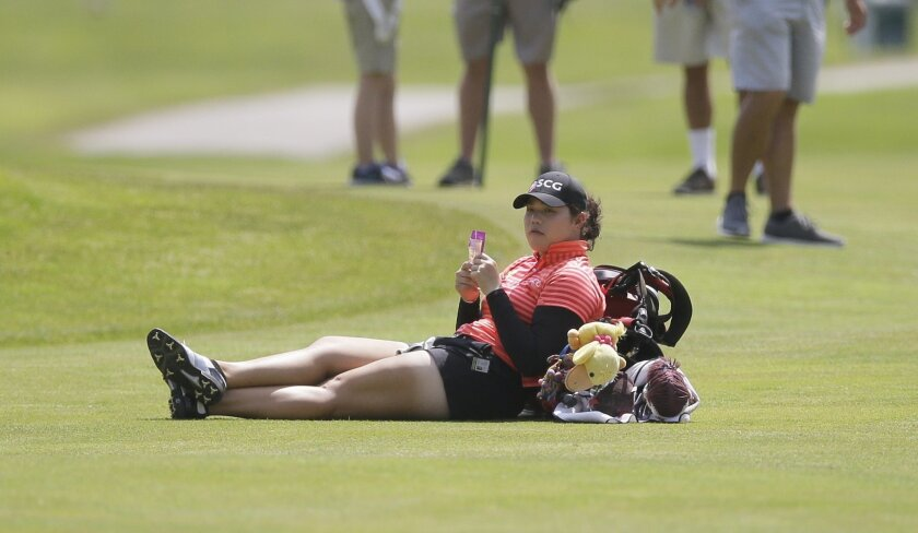 Ariya Jutanugarn, of Thailand, takes a break on the sixth fairway as play backs up during the third round of the LPGA Volvik Championship golf tournament at the Travis Pointe Country Club, Saturday, May 28, 2016, in Ann Arbor, Mich. (AP Photo/Carlos Osorio)
