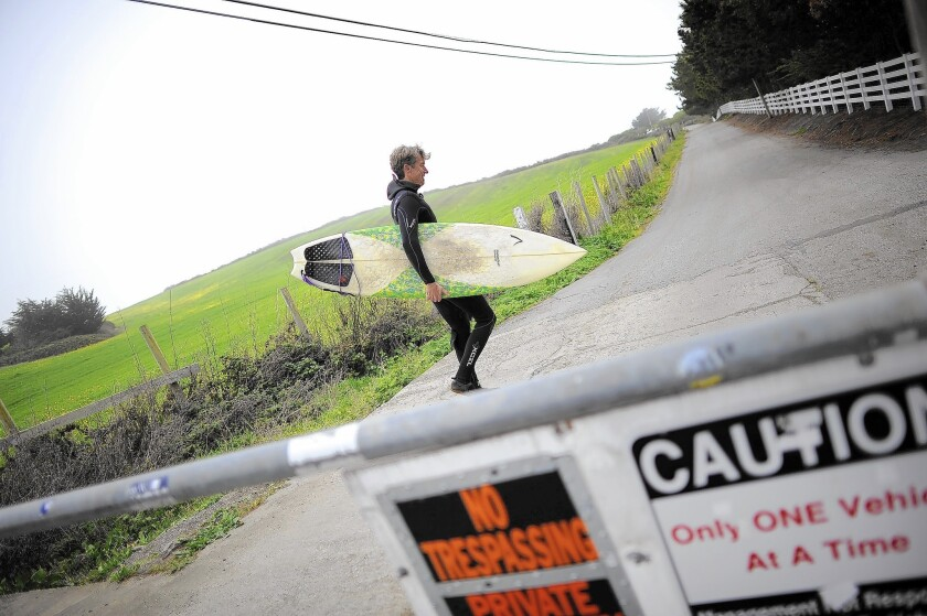 A surfer walks past the gate on his way to Martin's Beach near Half Moon Bay, Calif., in 2013. A judge ruled Wednesday that property owner Vinod Khosla wrongly denied access to the beach, but rejected a request that he be fined up to $20 million.