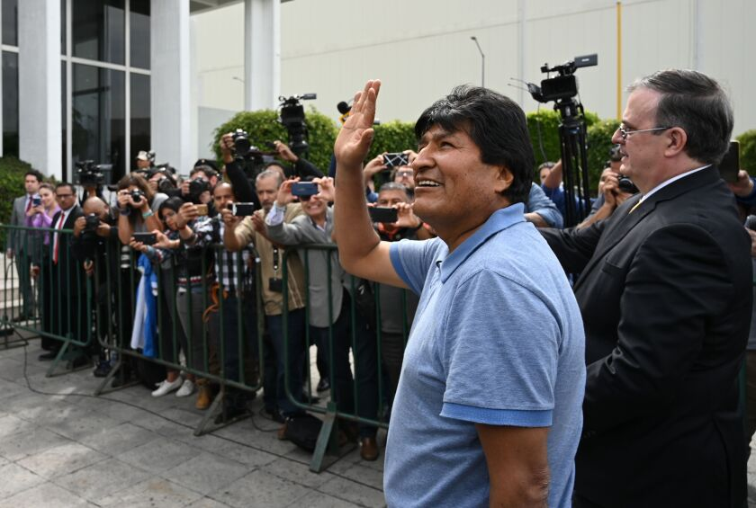 Former Bolivian President Evo Morales waves to spectators as he walks with Mexican Foreign Minister Marcelo Ebrard after arriving in Mexico City on Tuesday.
